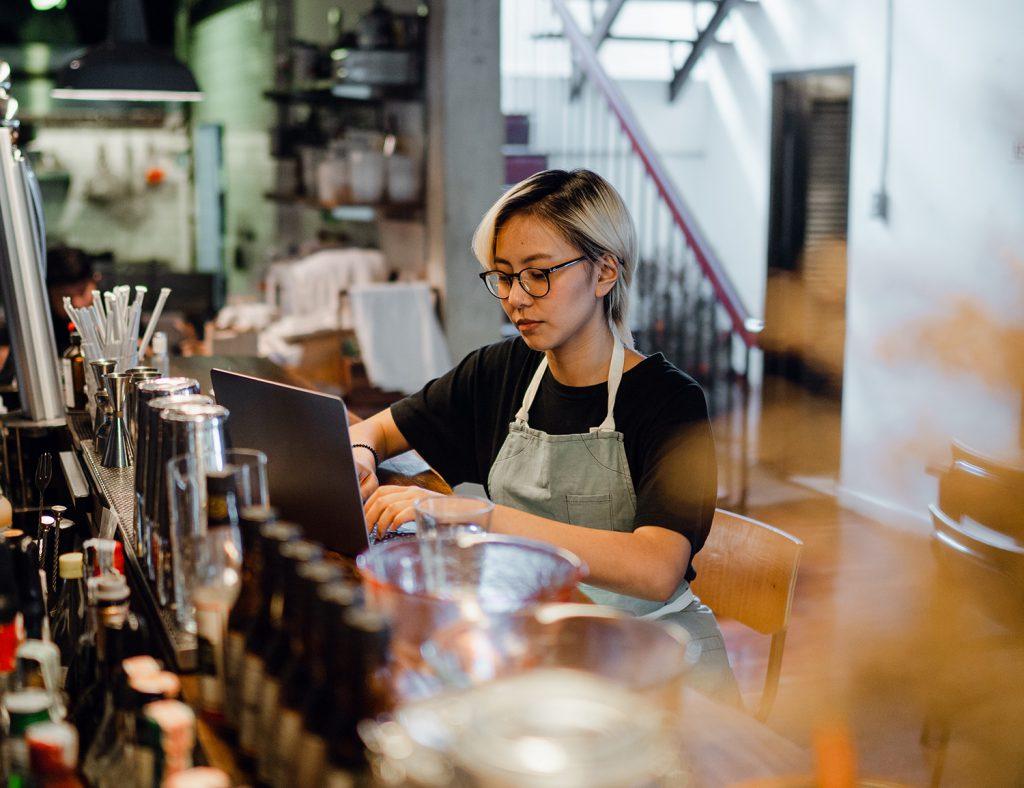 Restaurant or bar operator using Focus on her laptop.